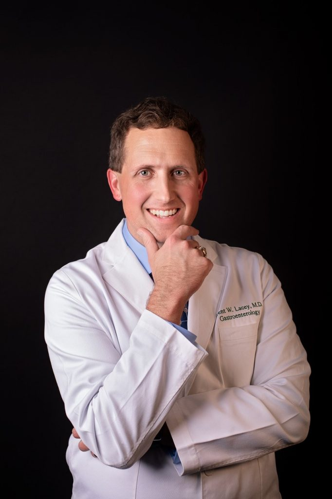 A portrait of Dr. Brent Lacey wearing his white coat and smiling